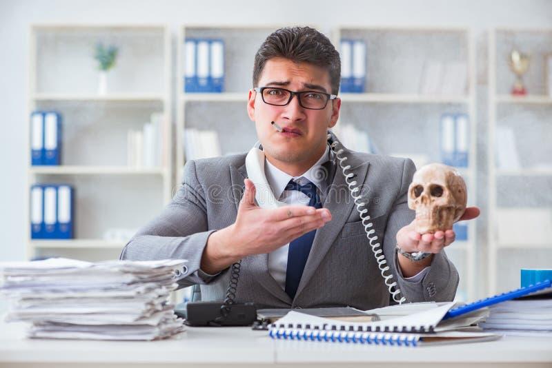L'homme d'affaires dans le bureau fumant tenant le crâne humain images stock