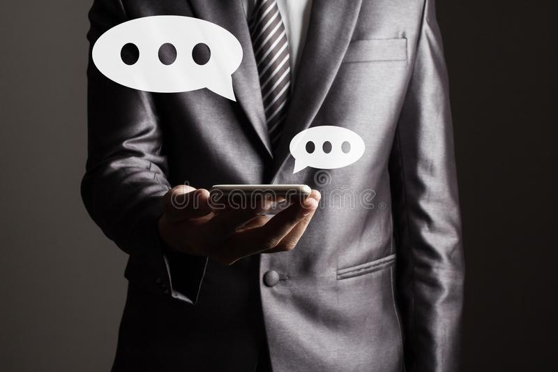 L'homme d'affaires dans le costume gris tenant le comprimé touchant le concept social de technologie de media photographie stock libre de droits