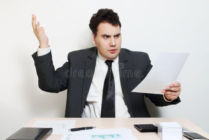 L'homme d'affaires dans le costume a outragé et des regards au document images stock