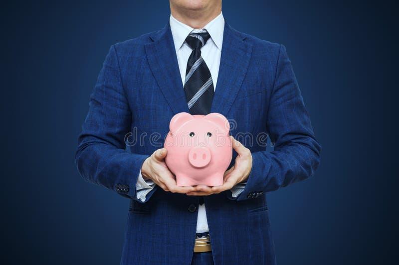 L'homme d'affaires dans le costume tient la tirelire Tirelire de porc de participation d'homme d'affaires Concept de l'épargne de photographie stock