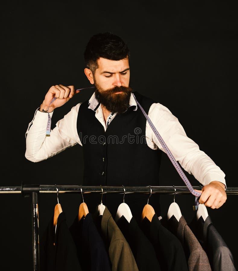 L'homme d'affaires dans le gilet classique mesure la taille de veste avec la bande de mesure photo libre de droits