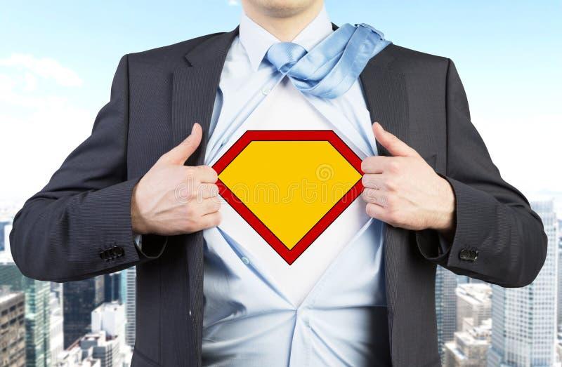L'homme d'affaires dans un costume déchire la chemise Chiffre jaune sur le coffre comme symbole de la puissance et du succès photo stock