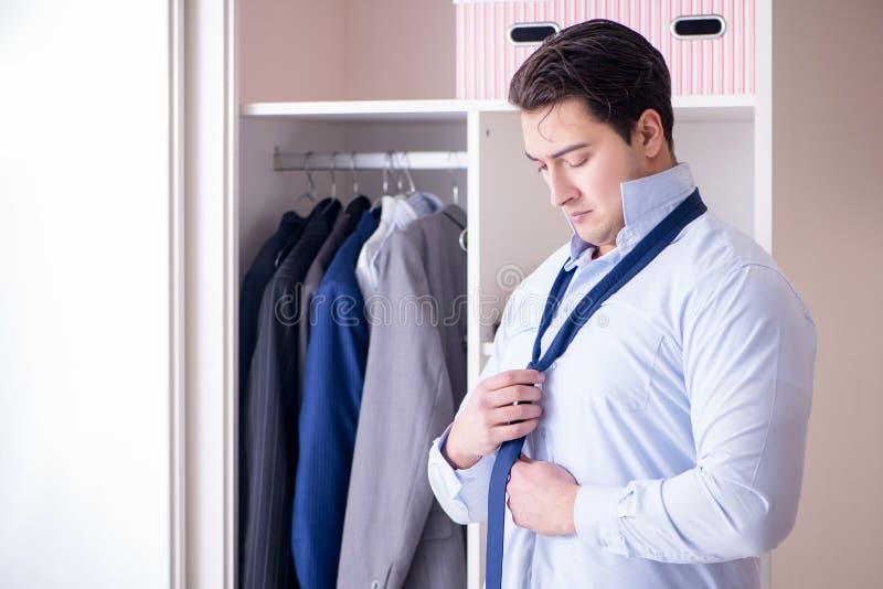 L'homme d'affaires de jeune homme obtenant habillé pour le travail images libres de droits