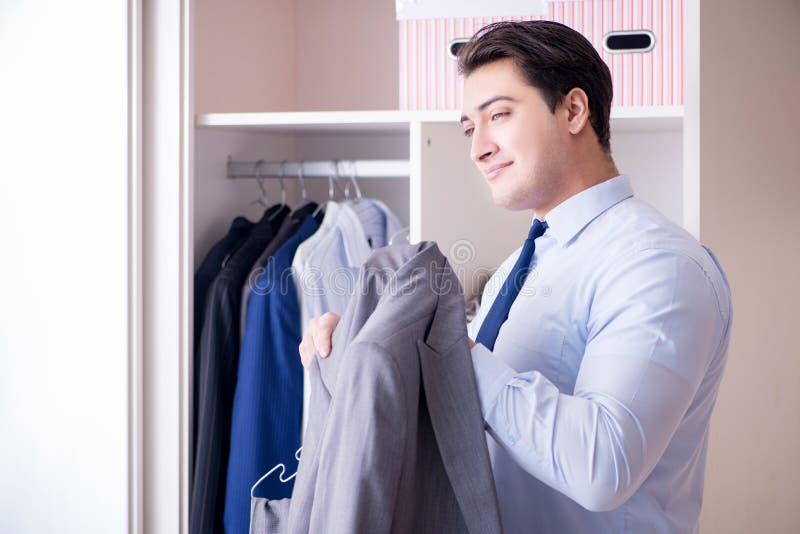 L'homme d'affaires de jeune homme obtenant habillé pour le travail photos stock