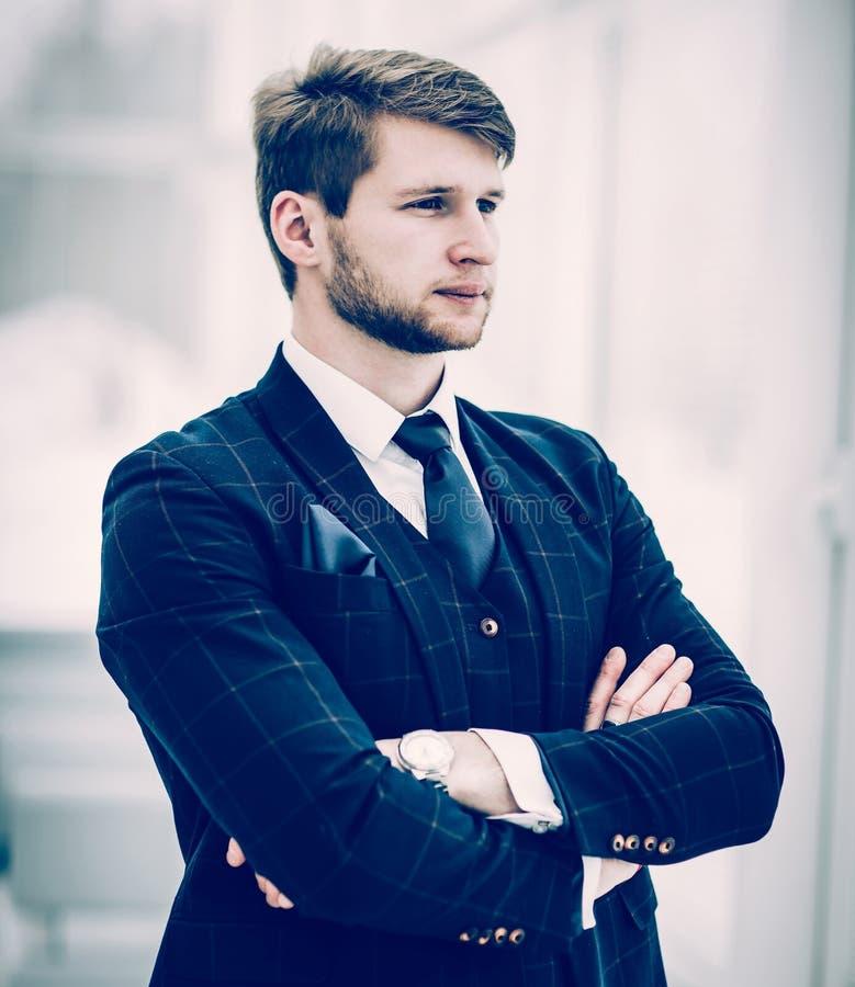 L'homme d'affaires de nouveau venu dans un costume se tient près de la fenêtre, photo stock
