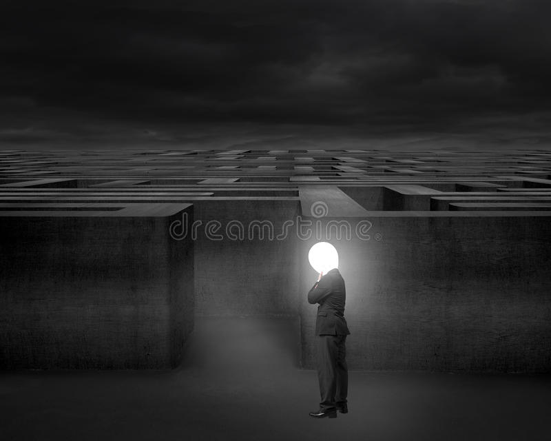 L'homme d'affaires de pensée avec la tête lumineuse de lampe a illuminé le labyrinthe foncé photographie stock libre de droits