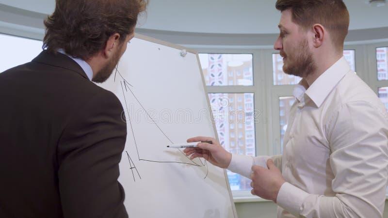 L'homme d'affaires dessine sur le tableau de conférence photographie stock libre de droits