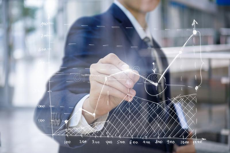 L'homme d'affaires dessine un programme de finances images stock