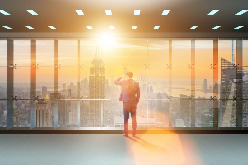 L'homme d'affaires devant la fenêtre de bureau pensant à de nouveaux défis photos libres de droits