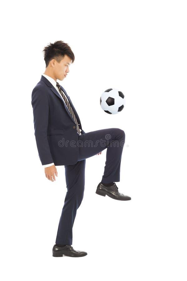 L'homme d'affaires donne un coup de pied un football photographie stock