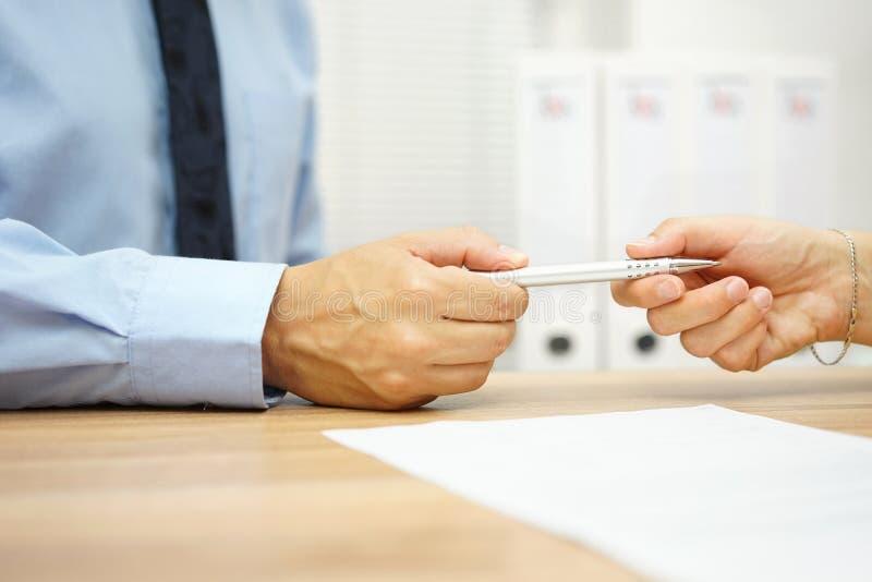 L'homme d'affaires donnent le stylo au client d'affaires pour signer les WI de contrat image libre de droits