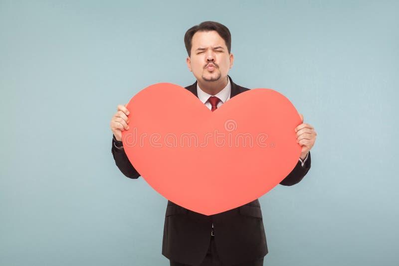 L'homme d'affaires drôle tenant le grand coeur rouge et envoient le baiser photos stock