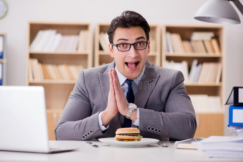 L'homme d'affaires drôle affamé mangeant le sandwich à nourriture industrielle images libres de droits