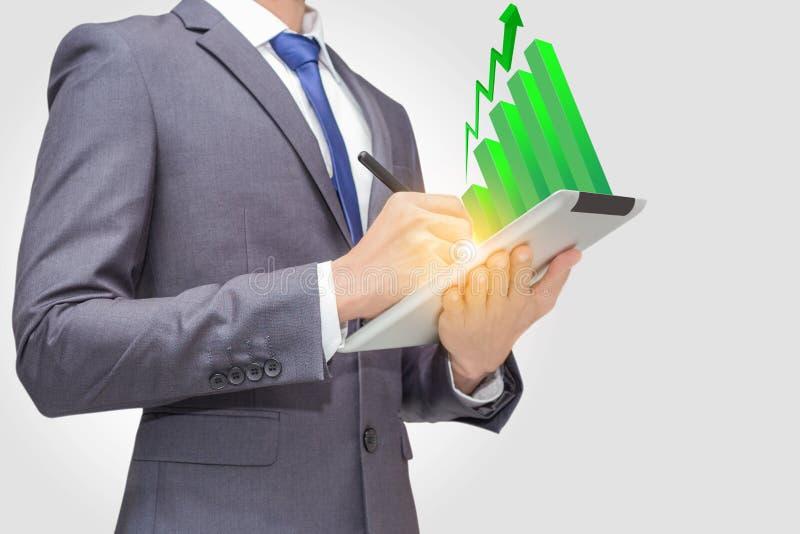 L'homme d'affaires employant le touchpad, comprimé pour rechercher et analyser des données avec le bâton vert représentent graphi images stock