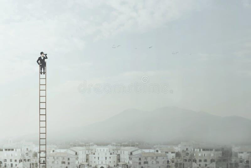 L'homme d'affaires en haut d'une longue échelle observe la ville avec ses jumelles photographie stock
