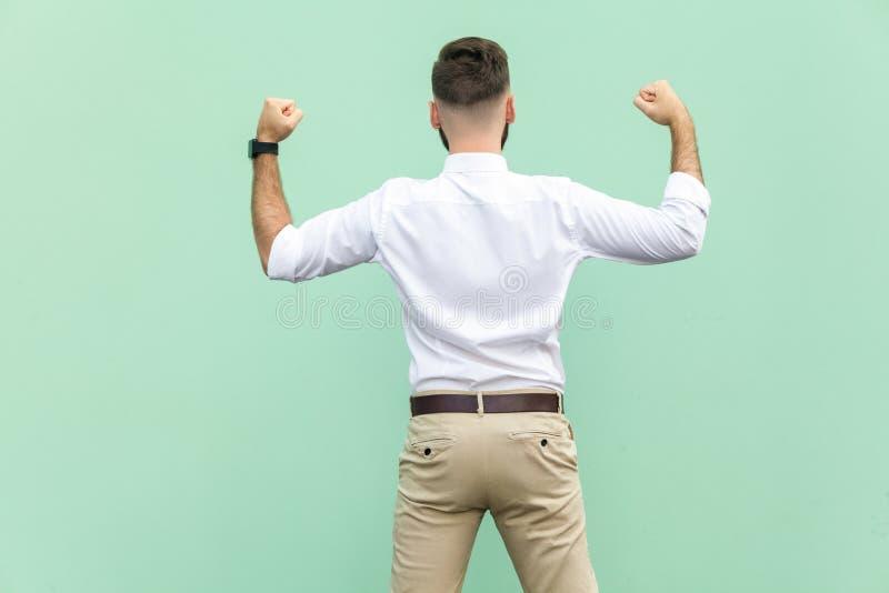 L'homme d'affaires enthousiaste célèbre un accomplissement de carrière Vue arrière d'un jeune homme d'affaires adulte, sur le fon photographie stock