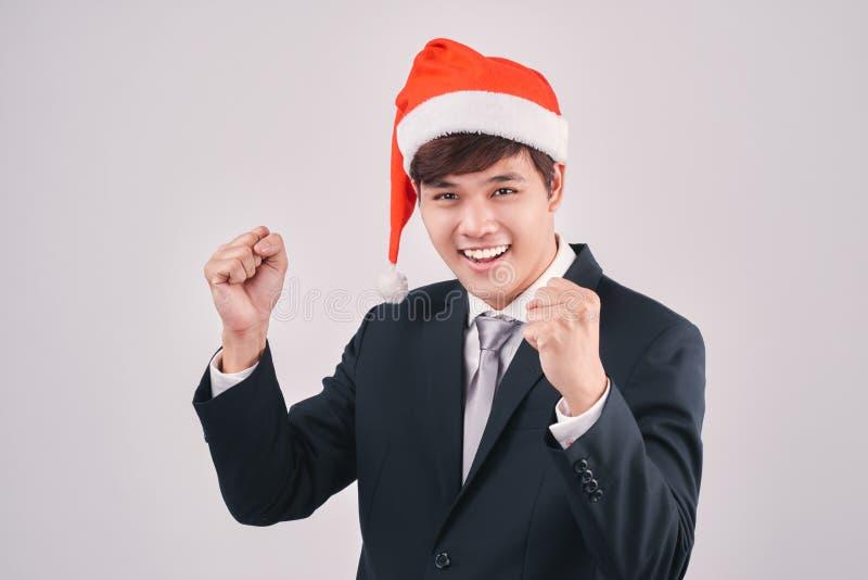 L'homme d'affaires enthousiaste dans le costume et le chapeau noirs de Santa isoalted sur le petit morceau photographie stock