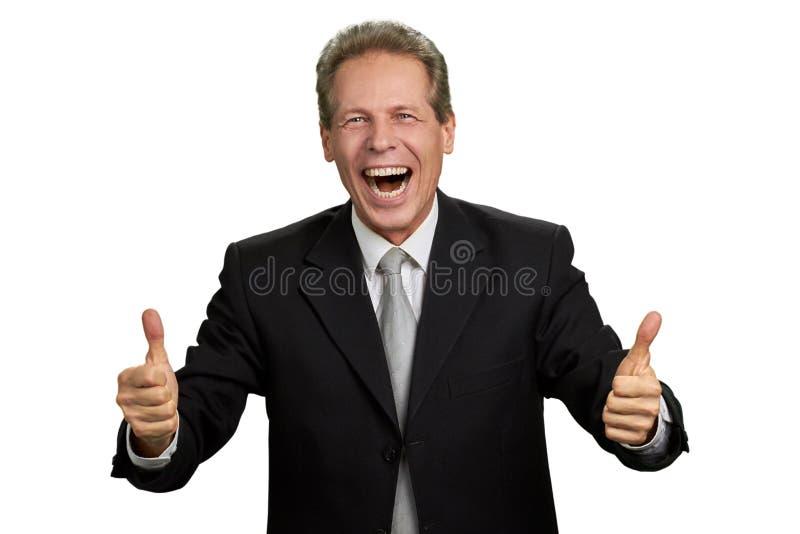 L'homme d'affaires enthousiaste heureux avec des pouces lèvent le geste photo stock