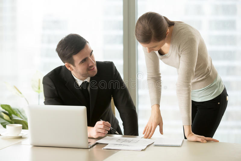 L'homme d'affaires et la femme d'affaires négociant au-dessus du bâtiment prévoient, des Di photos stock