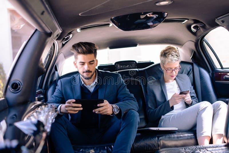 L'homme d'affaires et la femme d'affaires regardant l'iat téléphonent dans la limousine images libres de droits