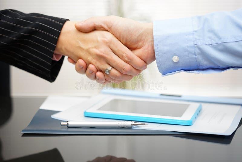 L'homme d'affaires et la femme d'affaires sont poignée de main au-dessus des documents et photo stock