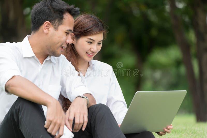 L'homme d'affaires et la femme utilisent l'ordinateur portable dans le parc, se reposent sur l'herbe ensemble photo stock
