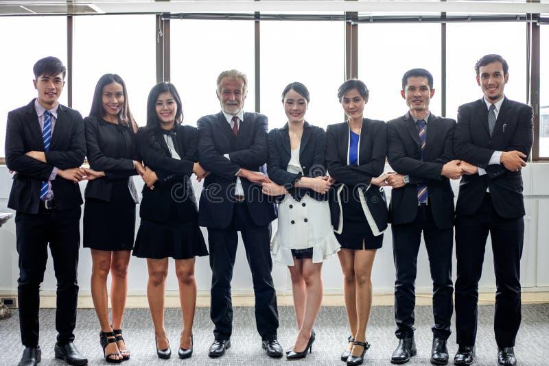 L'homme d'affaires et les femmes d'affaires heureux de sourire c?l?brant le bras d'accomplissement de succ?s ont augment? et le p images stock