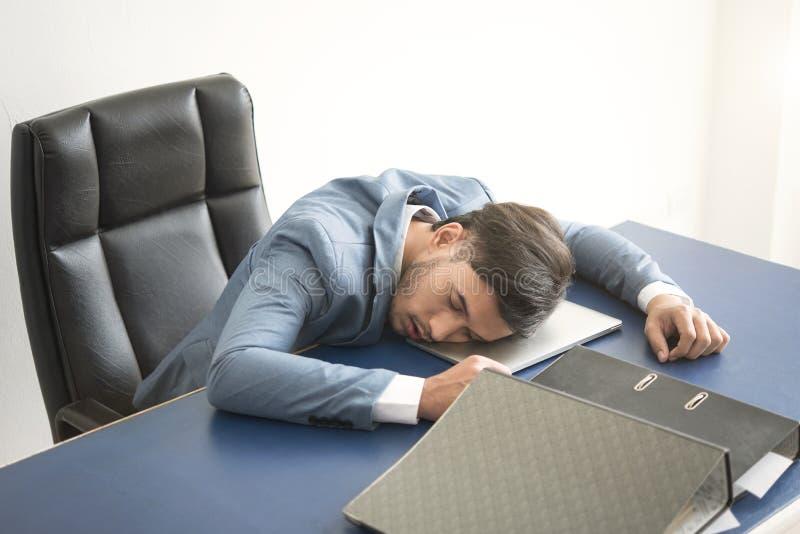 L'homme d'affaires a fatigué le sommeil surchargé au-dessus d'un ordinateur portable dans le bureau photographie stock libre de droits