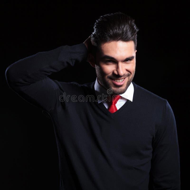 L'homme d'affaires fixe ses cheveux image stock