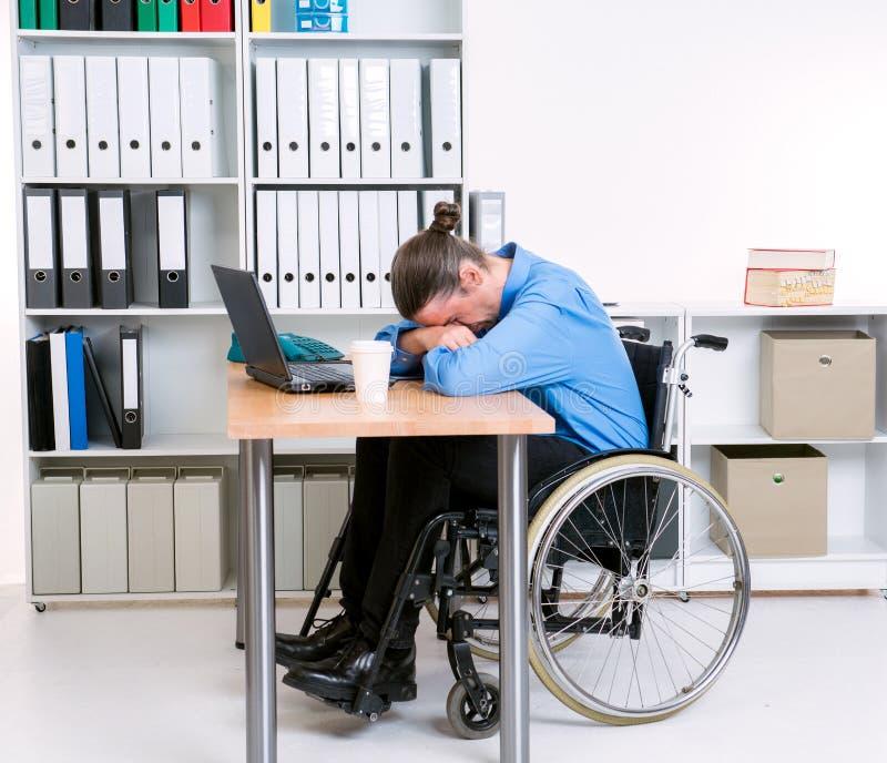 L'homme d'affaires handicapé dans le fauteuil roulant est déprimé photo stock