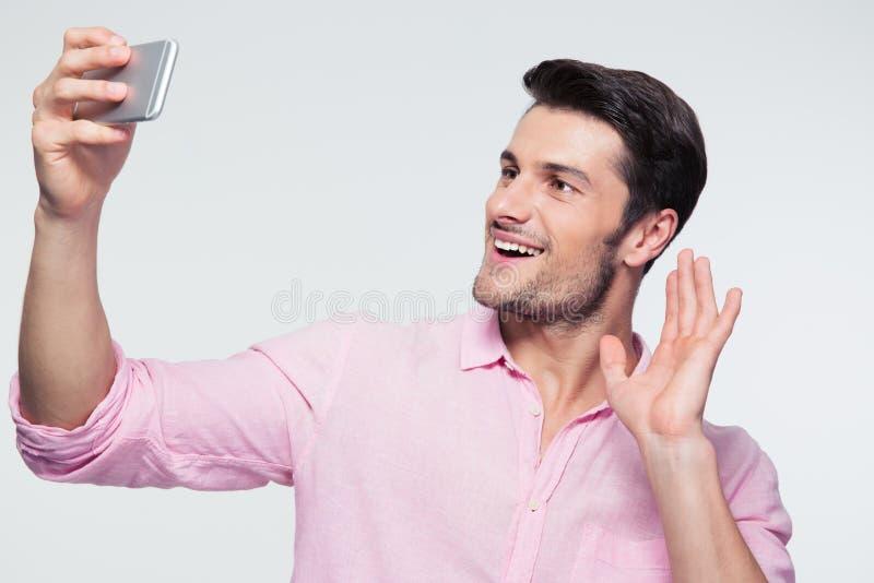 L'homme d'affaires heureux montrant la salutation se connectent le smartphone image libre de droits