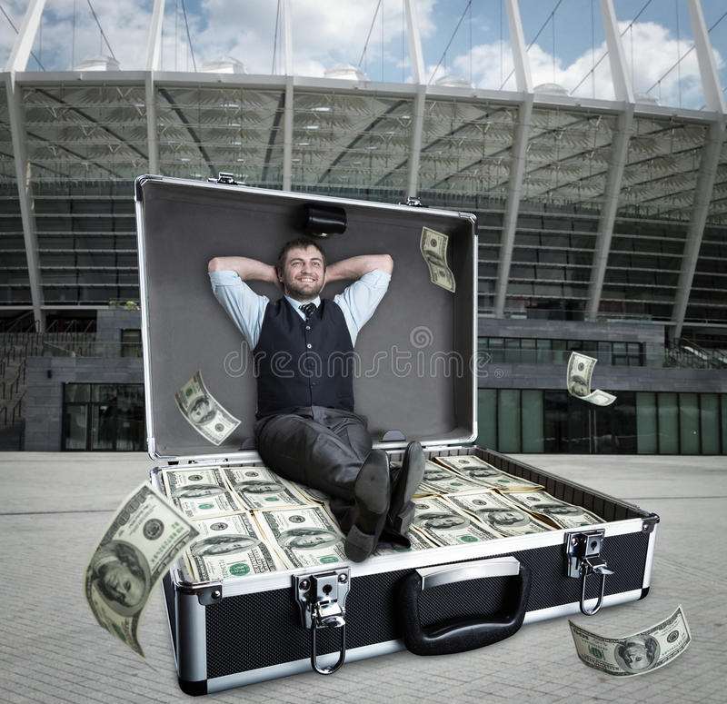 L'homme d'affaires heureux s'assied dans le cas complètement des dollars images libres de droits