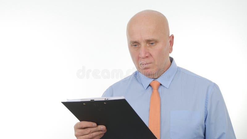 L'homme d'affaires Image Looking dans le presse-papiers a lu avec les documents techniques d'attention photographie stock