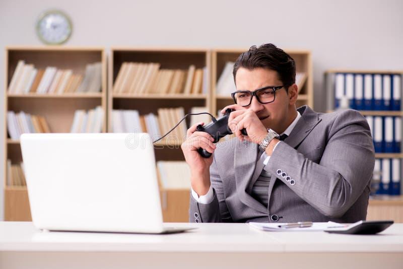 L'homme d'affaires jouant des jeux d'ordinateur au bureau de travail images stock