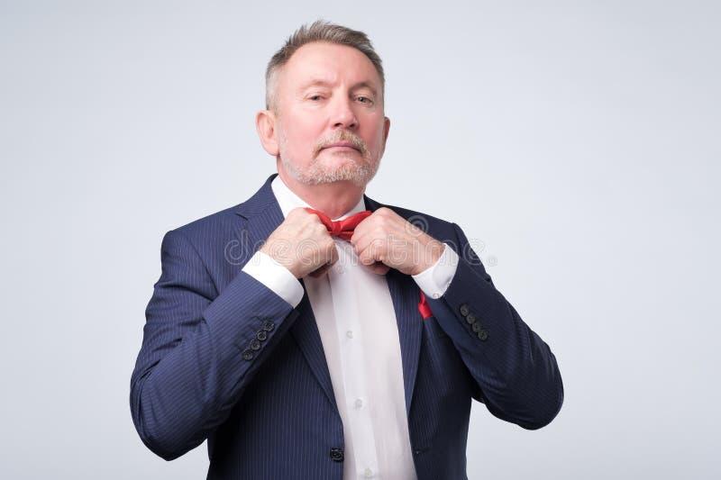 L'homme d'affaires mûr bel dans le costume formel ajuste son lien photographie stock