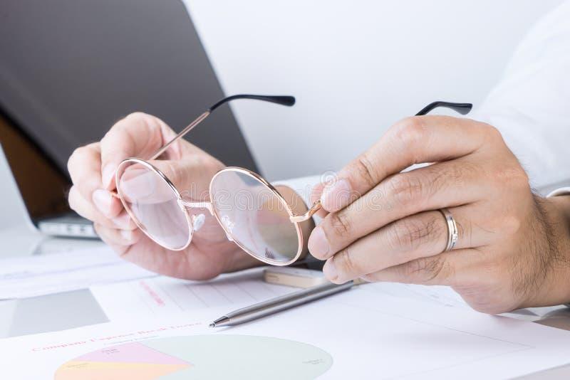 L'homme d'affaires met sur ses verres d'oeil photos stock