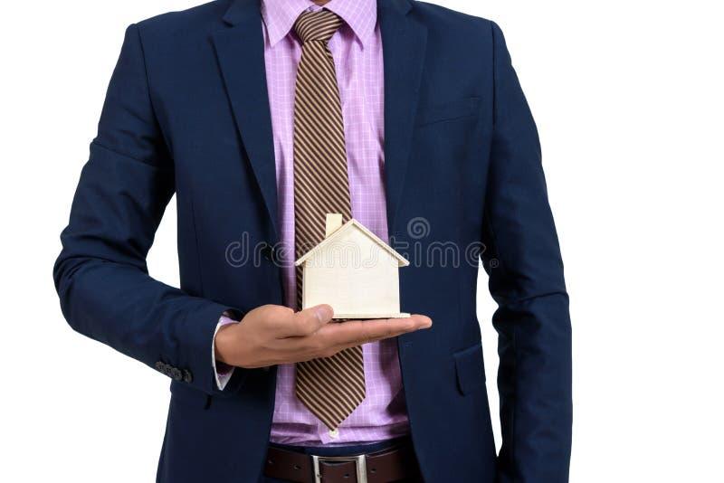 L'homme d'affaires met une maison en bois dans sa main conce d'affaires photo libre de droits