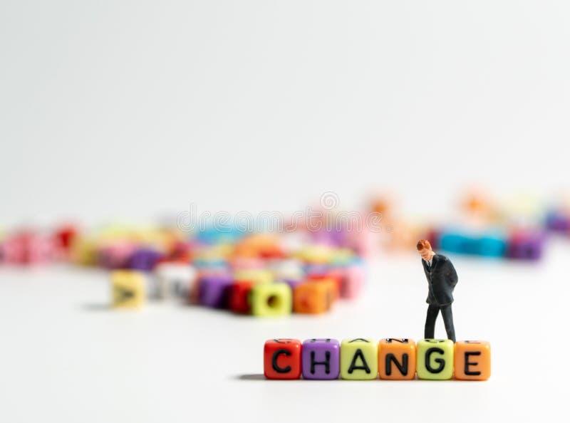 L'homme d'affaires miniature de figure dans le postérieur de position de costume bleu-foncé de coloré de l'alphabet de CHANGEMENT photos libres de droits