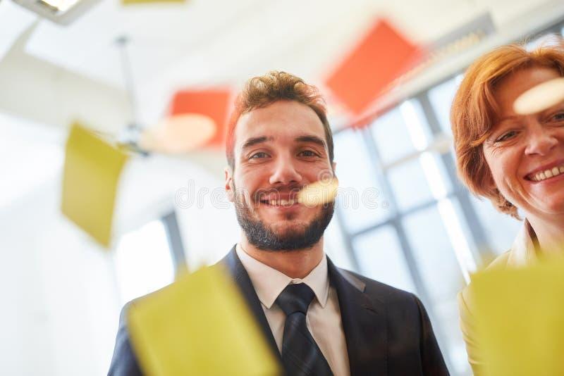 L'homme d'affaires a mis les notes collantes sur le verre image libre de droits