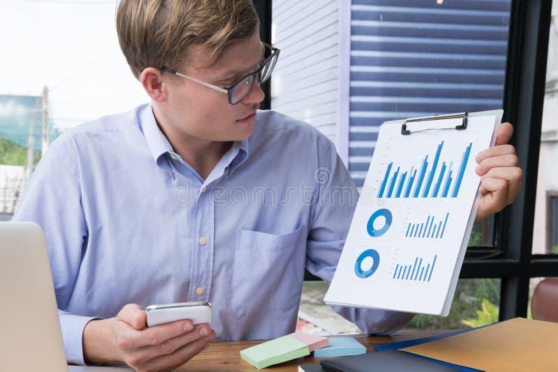 L'homme d'affaires montre le diagramme financier de graphique au bureau jeune homme p images stock