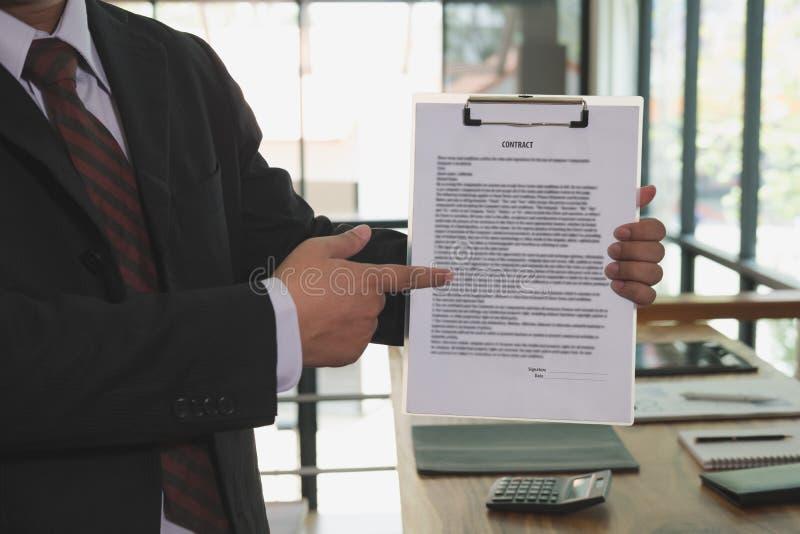 L'homme d'affaires montre le document d'accord contractuel de signe, affaires photo stock