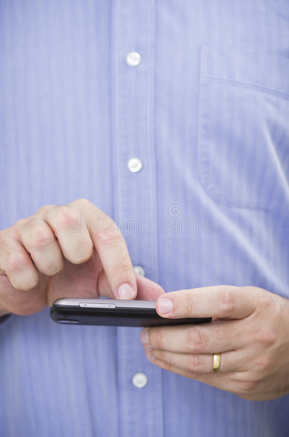 L'homme d'affaires occasionnel actionne un smartphone d'écran tactile image stock