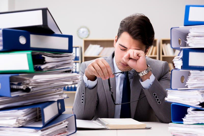 L'homme d'affaires occupé sous l'effort dû au travail excessif photos stock