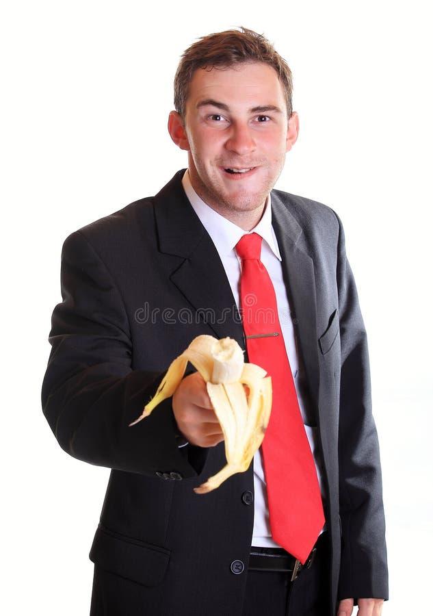 L'homme d'affaires offre une banane photos stock