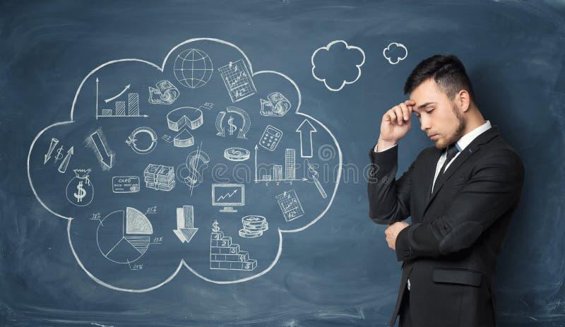 L'homme d'affaires pensant sur le fond du tableau noir avec des affaires gribouille images libres de droits