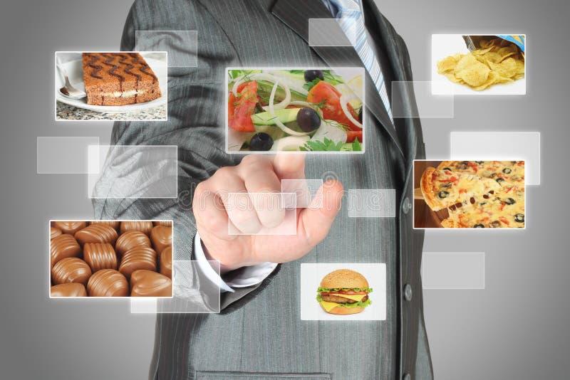 L'homme d'affaires pousse le bouton d'écran tactile avec de la salade sur l'interface virtuelle avec la nourriture photographie stock libre de droits