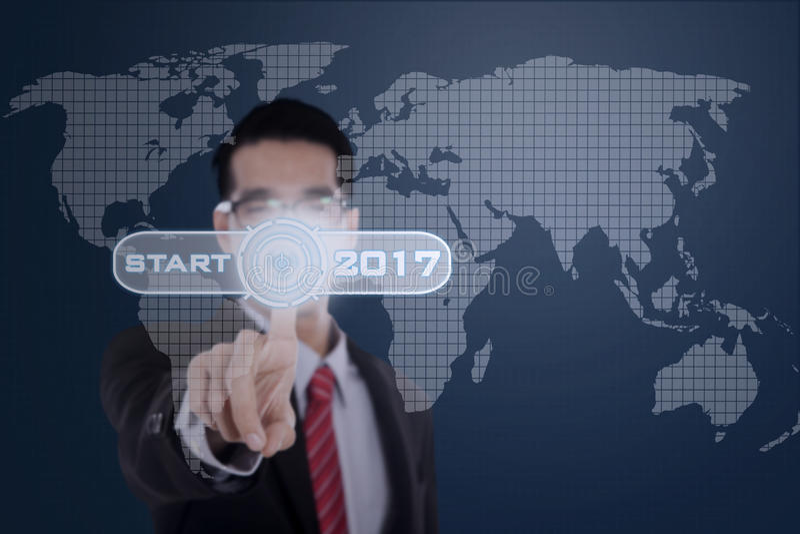 L'homme d'affaires presse le bouton marche avec 2017 photo stock