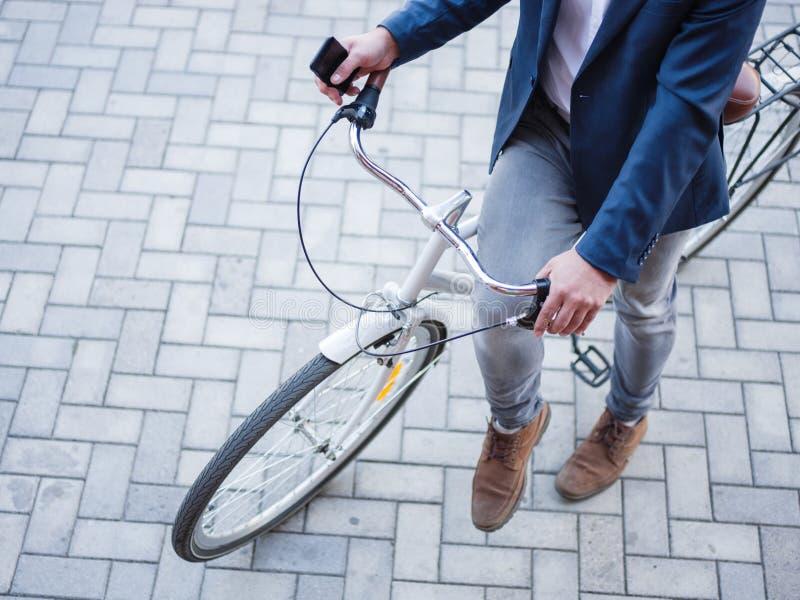L'homme d'affaires a pris le vélo et va travailler avec lui photographie stock libre de droits