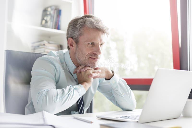 L'homme d'affaires réfléchi de sourire avec des mains a étreint regarder l'ordinateur portable dans le bureau photographie stock libre de droits
