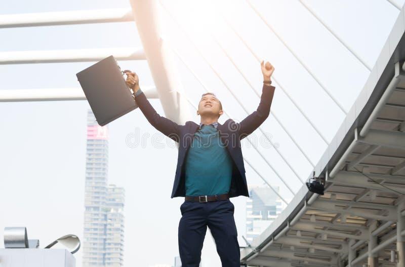 L'homme d'affaires réussi avec des bras se lèvent et tenant le brie en cuir images stock